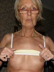 Elegant slim granny posing naked in..
